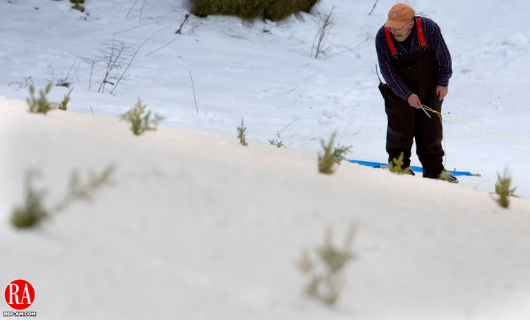 SALISBURY, CT- 08 FEBRUARY 2008- 020808JT03- Salisbury Winter Sports Association president Ken Barker lines up pine bows on the slope at Satre Hill in Salisbury before the opening night of Jumpfest weekend on Friday. Josalee Thrift / Republican-American