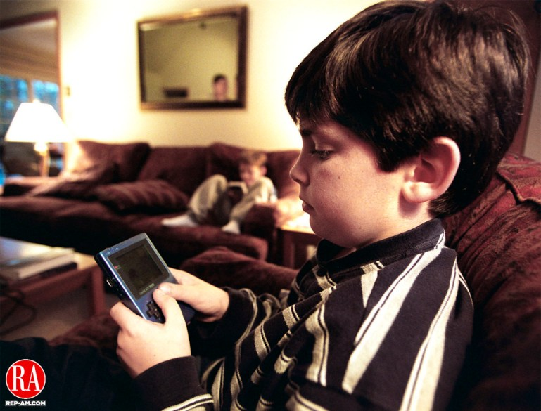 WOODBURY, CT.--10/27/98--1027MA06.TIF--Dan Emmons, 10, of Woodbury plays with his computer game, Pokemon as his brother Tom plays a different version of the game( background) MICHAEL ASARO staff photo for Accent story