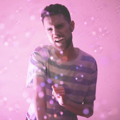 Photo of man standing against pink backdrop