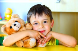 Smiling boy with a soft toy teddy bear