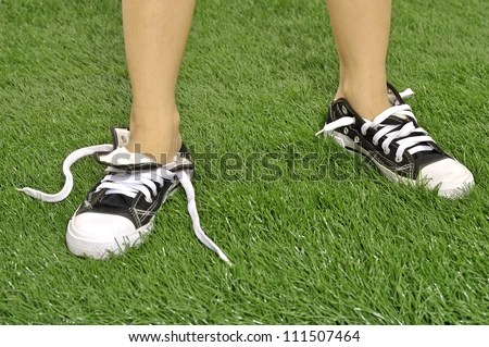 Kid with untied shoes on the green grass - stock photo