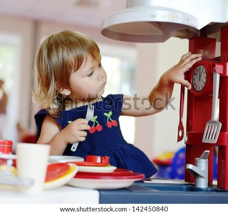 toddler girl playing toy kitchen - stock photo