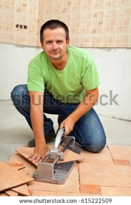 Man Cutting Ceramic Floor Tiles Manual Stock Photo  Royalty Free     Man cutting ceramic floor tiles with manual cutter   kneeling and smiling