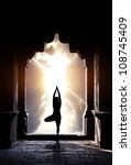 stock photo : Yoga vrikshasana tree pose by man silhouette in old temple arch at dramatic sunset sky background. Free space for text