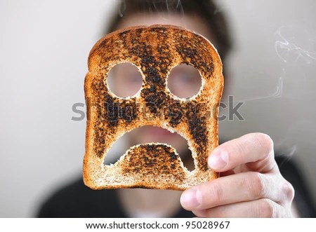 Man holding up a burnt slice of toast with an unhappy smiley concept for bad start to the day - stock photo