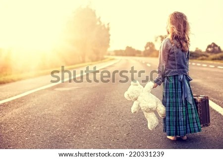 The girl in a dress with a suitcase looking at the sun - stock photo