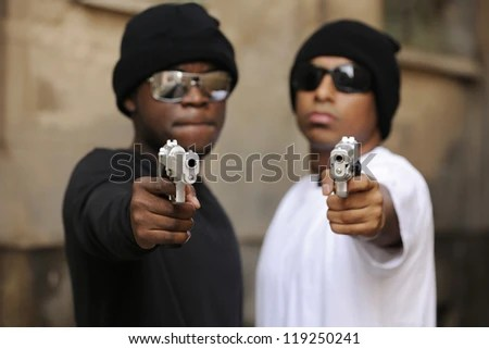 Gang members on the street, focus on guns - stock photo