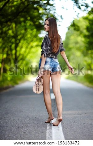 Sexy young woman walking along the road and looking over the shoulder