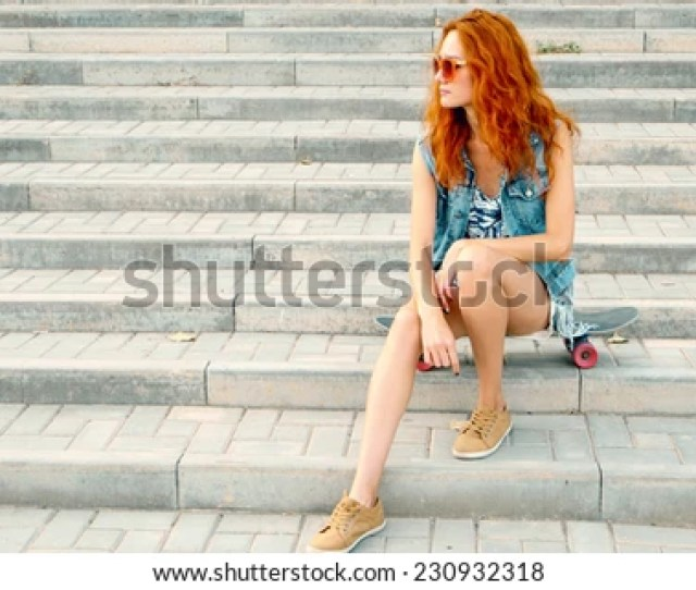 Young Teen Women Sitting On Stairs On Her Skateboard And Looking Away A Lot Of