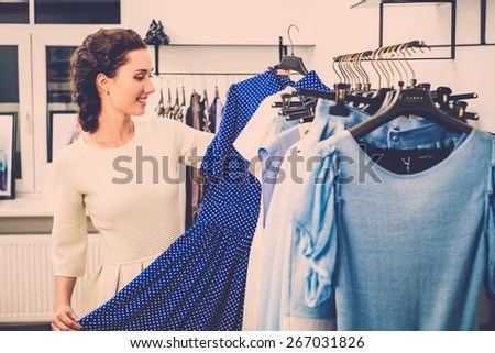 Young woman choosing clothes on a rack in a showroom  - stock photo