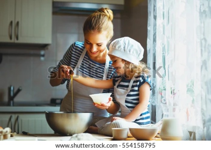 Top stock image websites. happy family in the kitchen. mother and child daughter preparing the dough, bake cookies