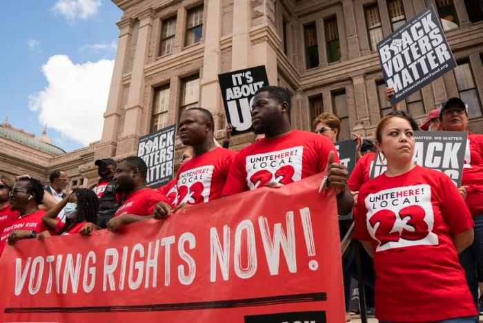 Individuals stand on the south steps of the Texas Capitol in support of voting rights at a press conference organized by Bla…