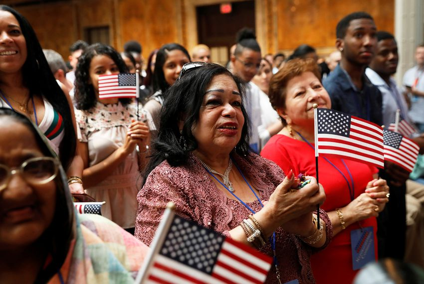 New citizens stand during a U.S. Citizenship and Immigration Services (USCIS) naturalization ceremony at the New York Public Library in Manhattan, New York, U.S., July 3, 2018.