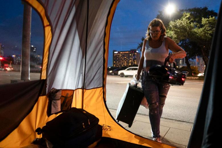 Christina Jezzizki, 58, starts preemptively moving her belongings to avoid being arrested for camping in front of Austin City Hall, but is interrupted by rain on July 10, 2021.  Source diversity info: White Female