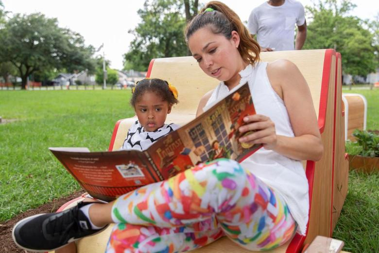 Alejandrina Flores Reyna reads to her daughter Sira during the unveiling of Violette Bule's public art installation 'Rethinking Your Neighborhood: A Collaborative Experience' in Houston, Texas on June 12, 2021.
