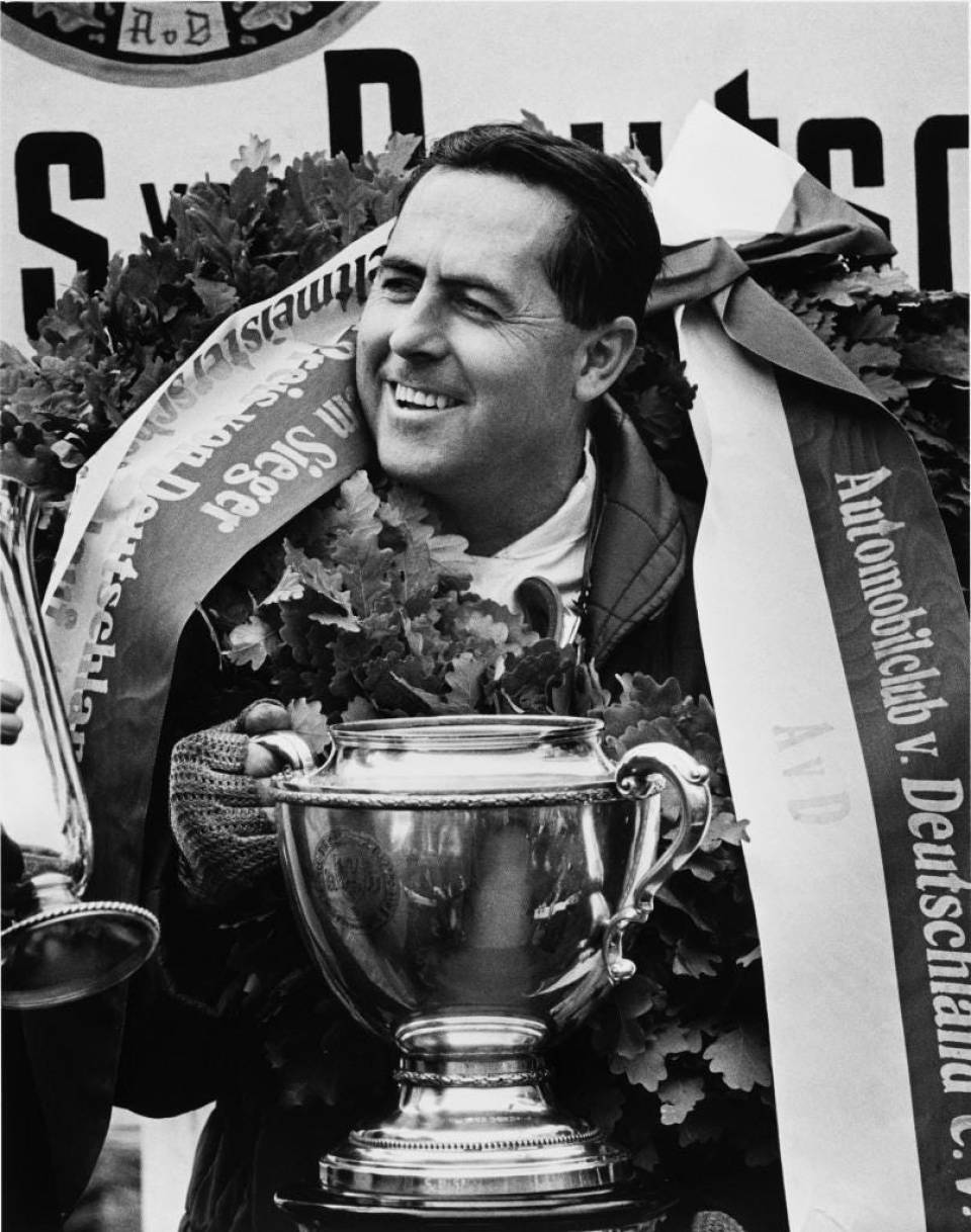 The Founder Of The Racing And Manufacturing Dynasty, Big Jack Brabham, Takes The Cup: Sir Jack on the podium after his triumphal F1 run at Nurburgring, Germany in August 1966, in the history-making Constructors' champion car, the BT19.