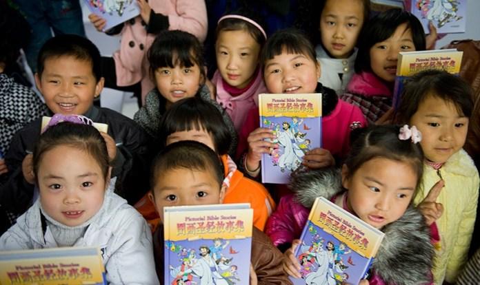 Crianças recebem literatura cristã infantil, distribuída por missionários, na China. (Foto: American Bible Society News)