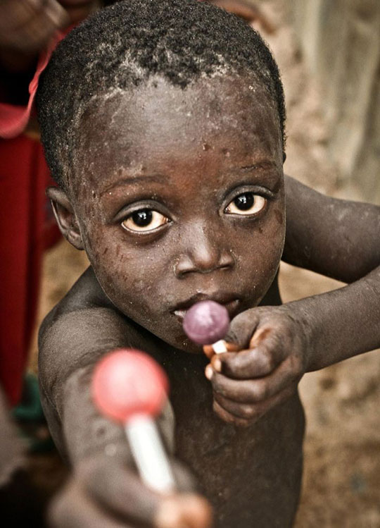 Child Offers To Share A Lollipop With The Photographer