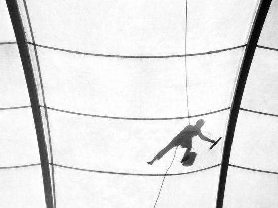 A daily wage worker's silhouette is seen as he cleans the roof of a four-storey shopping mall in India's capital Delhi while dangling from a rope.