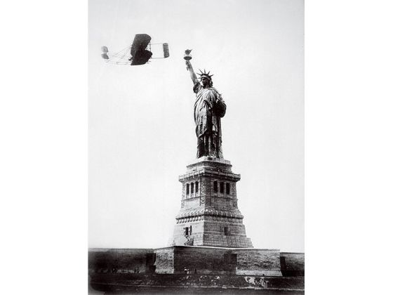 A wright plane passes by the Statue of Liberty