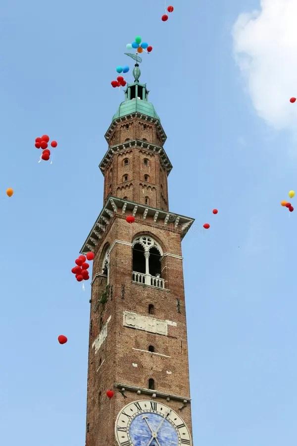 Башня с часами с красочными воздушными шарами во время ...