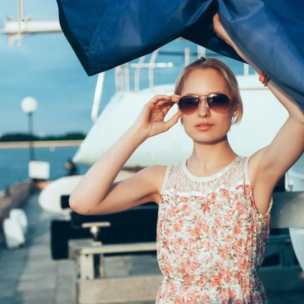 Белокурая девушка в платье и солнечных очках цветка держа ...