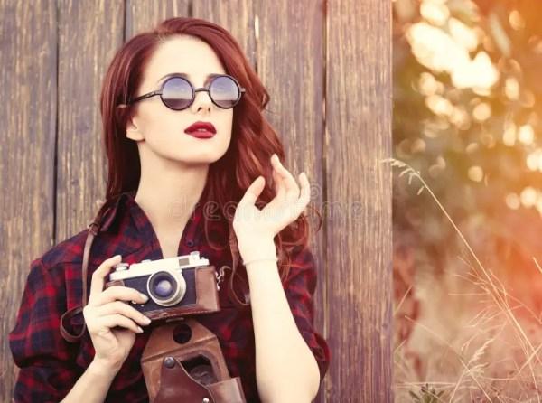 Девушка в платье шотландки с камерой и солнечными очками ...