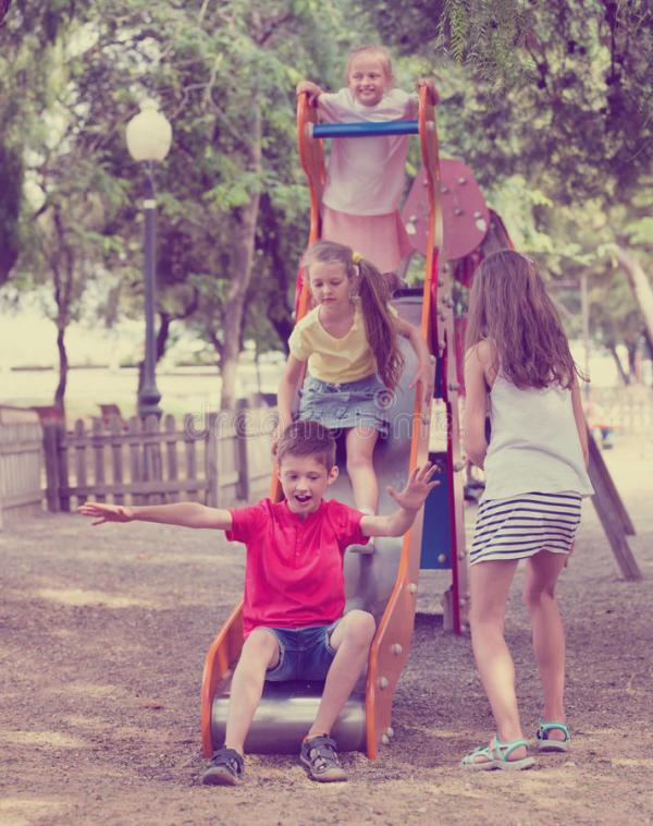 Дети сползая вниз совместно на конструкцию ` S спортивной ...