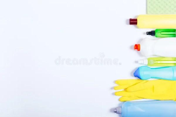 Желтые, голубые и зеленые бутылки с уборщиками, перчатками ...