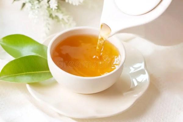 Закройте вверх по лить горячий черный чай в белой чашке ...