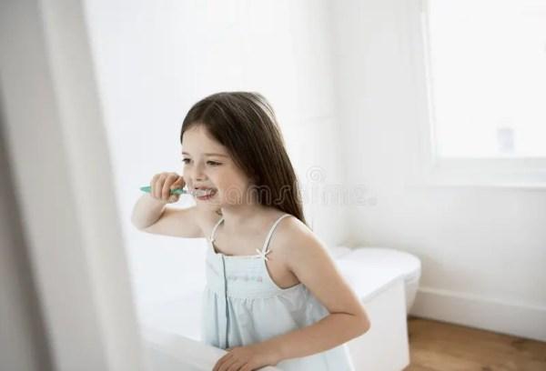 Зубы девушки чистя щеткой в ванной комнате Стоковое Фото ...