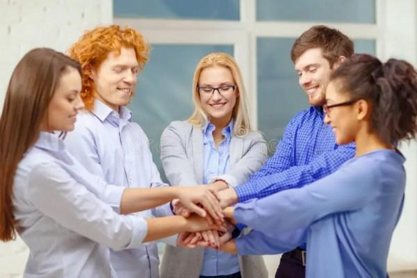 Команда с руками Na Górze одина другого в офисе Стоковое ...