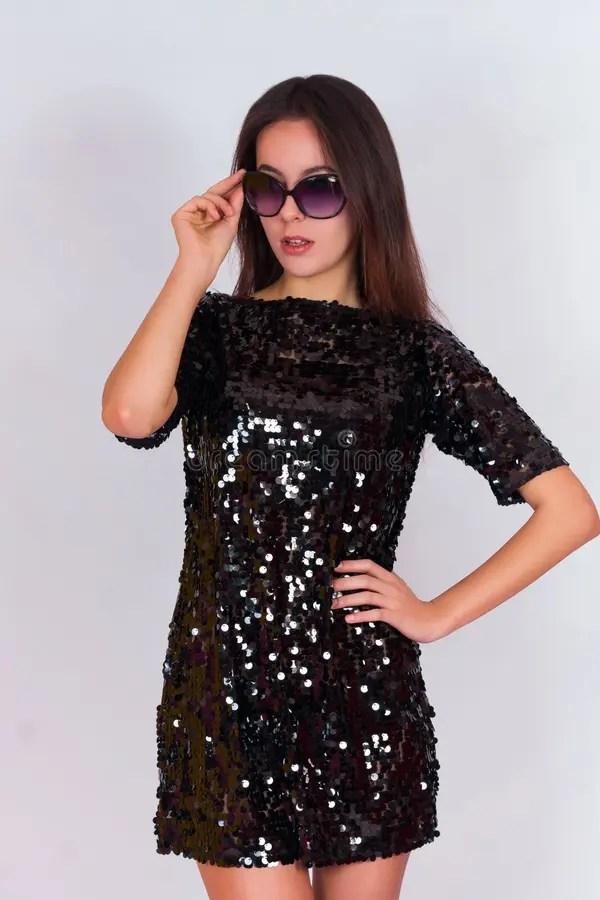 Красивая девушка брюнет в черном платье и солнечных очках ...