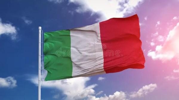 Национальный флаг, развевающийся на голубом небе Италии, с ...