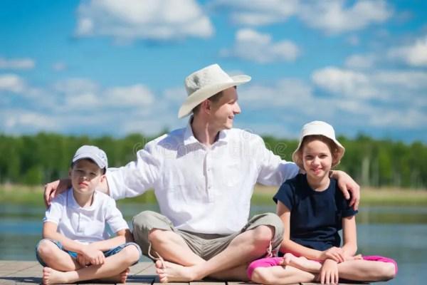Отец с дочерью и сыном сидит на красивой пристани на озере ...