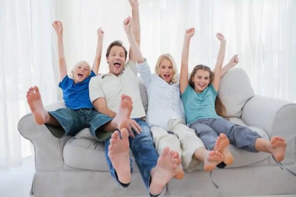 Семья сидя на софе и используя компьтер-книжку, таблетку и ...
