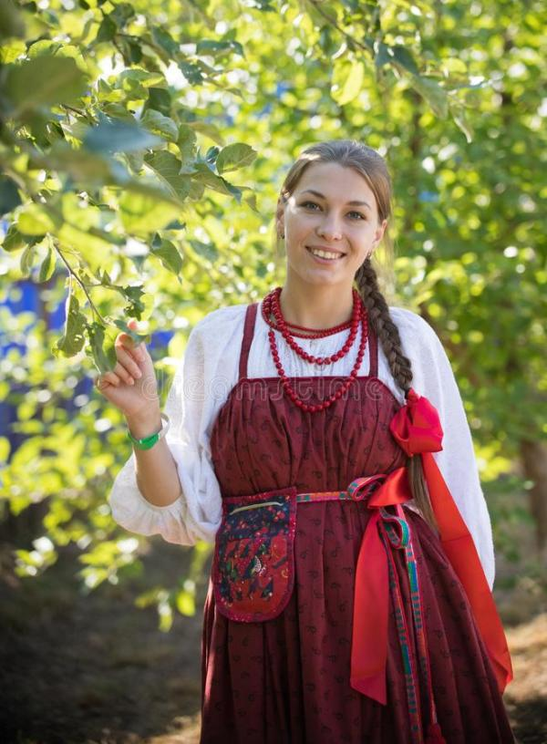 Красивая усмехаясь кавказская девушка в русском костюме ...