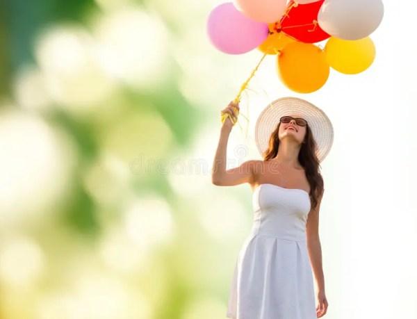 Усмехаясь молодая женщина в солнечных очках с воздушными ...