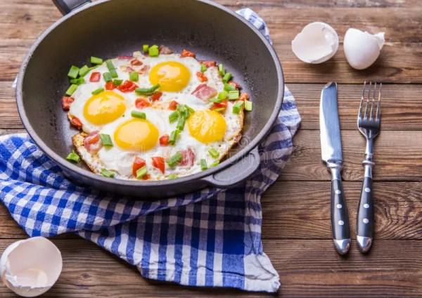 Фред Eggs в лотке с томатами и луком зеленого цвета свежим ...
