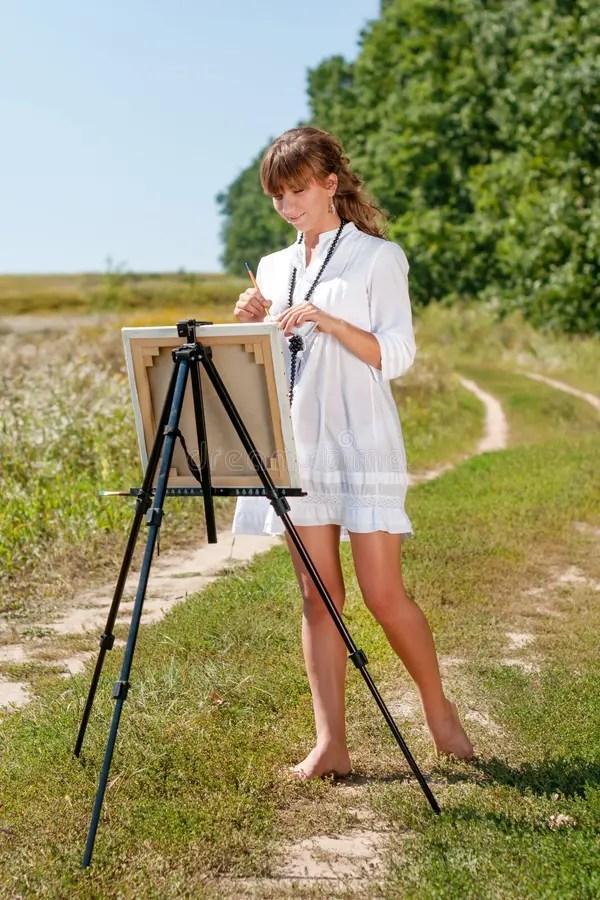 Художник молодой женщины на картине мольберта ...