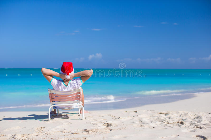 Back View Of Young Man In Santa Hat Relax At Beach Stock