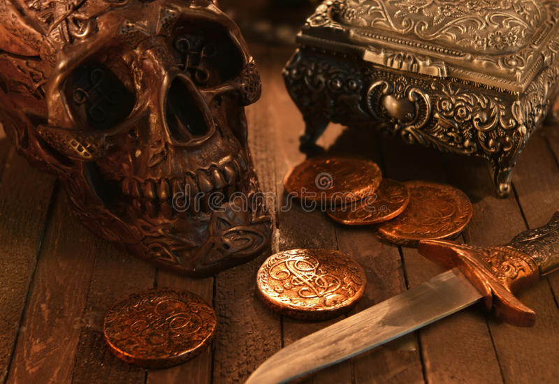 Black Skull Coins And Dagger In Candle Light Stock Photo