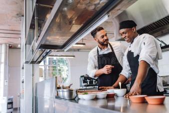 Chefs cooking food at cafe kitchen. Happy men chefs cooking food at cafe kitchen. Two cooks making food dishes in restaurant kitchen royalty free stock image
