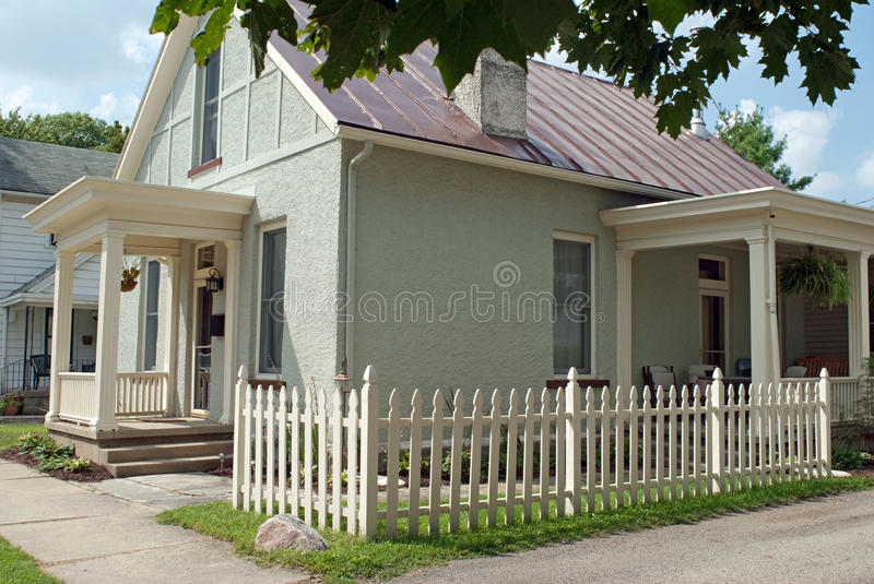 Corner Picket Fence With Small Stucco Cottage Stock Photo
