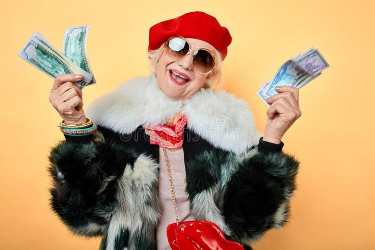 Elegant cheerful woman with raised arms showing her money. Rich female in red cap, fur coat, isolated yellow background, studio shot.crime concept stock photo
