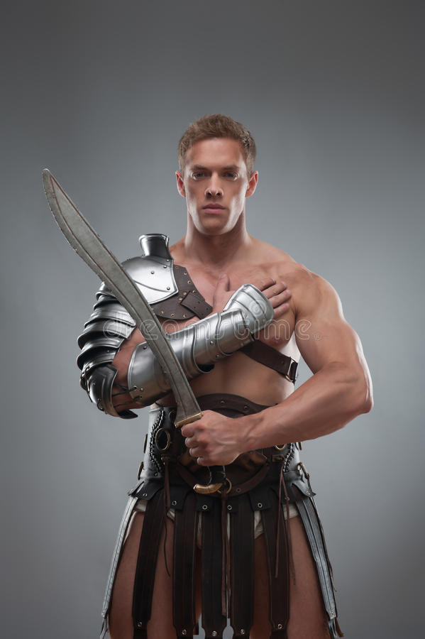 Gladiator In Armour Posing With Sword Over Grey Stock