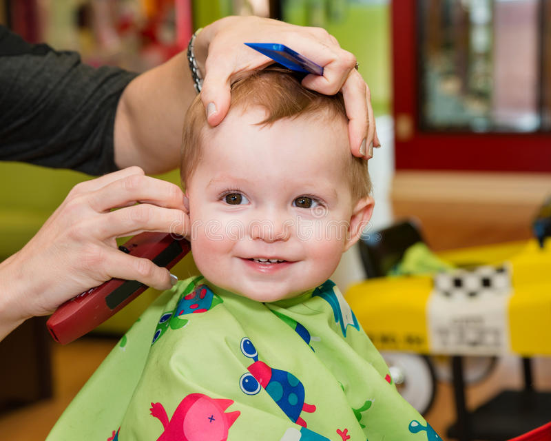 Happy Toddler Getting His First Haircut Stock Photo