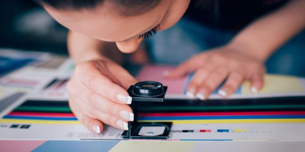 Worker In Printing And Press Centar Uses A Magnifying ...