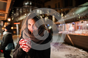 Long hair girl on European Christmas Market. Young woman Enjoying Winter Holiday Season. Blurred Lights background, dusk. Cups wi