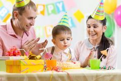 Child With Parents Blow Candle On Birthday Cake Stock ...